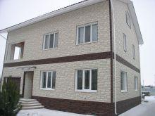 Загородный коттедж с облицовкой из сайдинга под камень белого и темного цветов